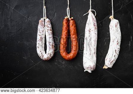 Spanish Salami, Fuet And Salchichon Sausages Hang From A Rack On Black Surface.