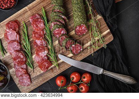 Spanish Fuet Salami Sausage Slices  On Balck Background, Flat Lay.