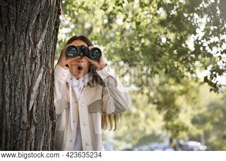 Young Woman With Binoculars Spying On Her Boyfriend In Park. Cheating Concept