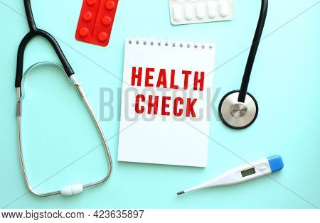 The Red Text Health Check Is Written On A White Notepad That Lies Next To The Stethoscope And Pills