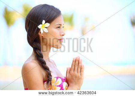 Serene meditation - meditating woman on beach smiling happy in profile on hawaiian beach. Beautiful portrait of mixed race Asian / Caucasian female model relaxing on Hawaii.
