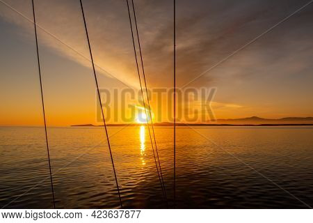 Orange Dramatic Sunrise Over The Sea With Bank Of Dark Clouds On The Sky Seen Through The Shrouds An