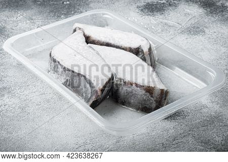 Frozen Greenland Halibut Steaks Vacuum Pack Set, On Gray Stone Table Background, With Copy Space For