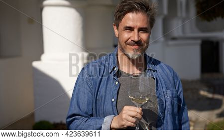 Happy man drinking wine outdoor holding wine glass, smiling. Wine tasting in vinery. Portrait of mature age, middle age, mid adult man in 50s.