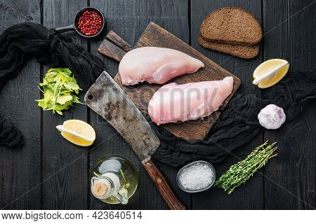 Crumbed Uncooked Chicken Breasts Ingredient With Butcher Knife  On Black Wooden Table, Top View