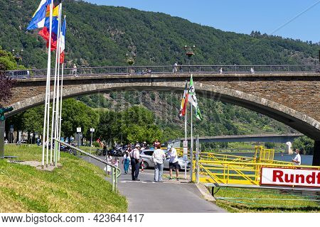 Cochem, Germany, June 13, 2021. People Walking On The Bridge And The Sidewalk Along The River In The