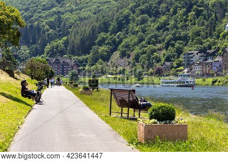 Cochem, Germany, June 13, 2021. People Sitting On Benches Along The River In The Tourist Destination