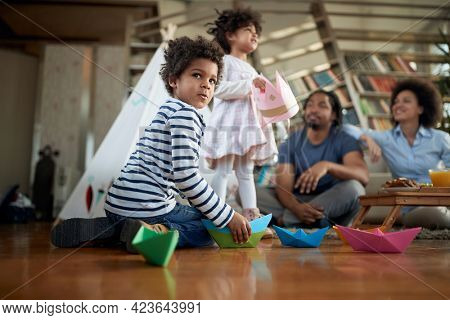 A little boy playing with his sister while spending time with their parents in a family atmosphere at home together. Family, home, together, playtime