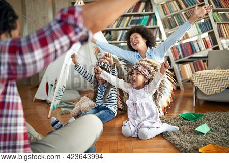 Excited kids with indian headdresses and their parents are yelling while imitating Indians in a cheerful atmosphere at home. Family, together, love, playtime