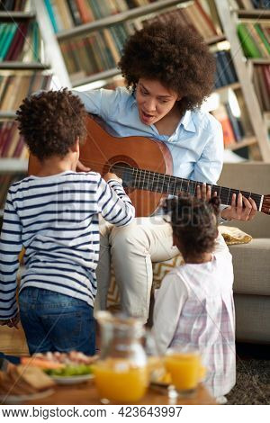 Young Mom playing the guitar to her children in a relaxed atmosphere at home. Family, together, love, playtime