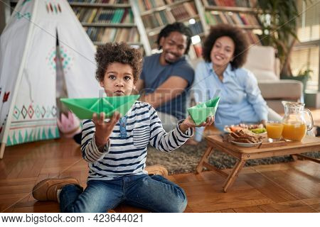 A little boy spending quality time with his parents in a family atmosphere at home. Family, home, together, playtime
