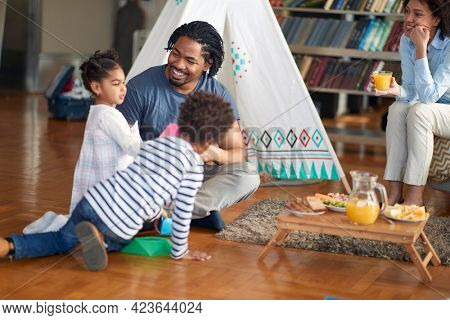 Happy family enjoying playtime in a relaxed atmosphere at home together. Family, together, love, playtime