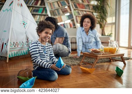 A little boy playing with paper boats and posing for a photo on the floor while spending time with his parents in a family atmosphere at home. Family, home, together, playtime