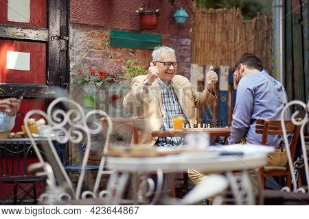 older caucasian male smiling with thumbs up. young guy with his hand over his eyes. sitting in outdoor cafe, playing chess. winning and loosing concept