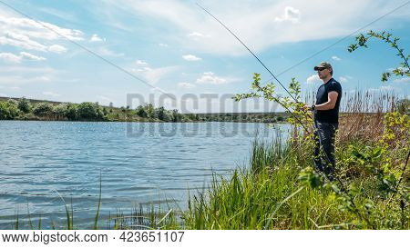 Fisherman With Spinning Rod On Nature Background. Angler Man With Fishing Spinning Or Casting Rod By