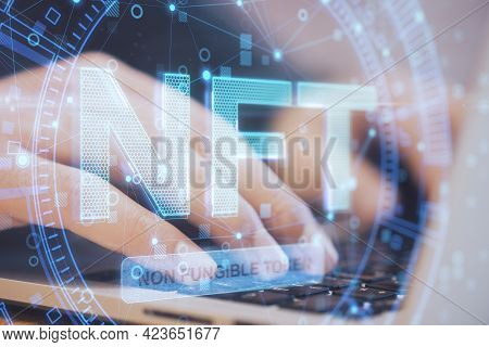Close Up Of Hands Using Laptop Computer Keyboard With Glowing Nft Non Fungible Token Concept Hologra