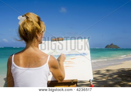 A Female Artist Painting On The Beach In Hawaii