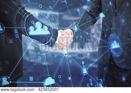 Businessmen Shaking Hands In Office With Creative Glowing Blue Business Interface On Blurry Backgrou