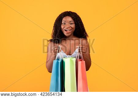 Excited Black Woman Holding Bright Shopping Bags, Posing And Looking At Camera, Happy With Her Summe