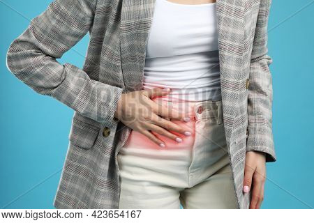 Woman Suffering From Appendicitis Inflammation On Light Blue Background, Closeup