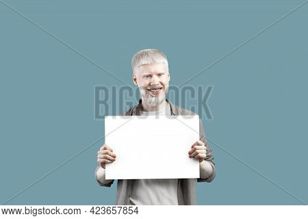 Cool Offer. Happy Albino Guy Holding Blank Poster With Empty Space, Standing Over Turquoise Studio B
