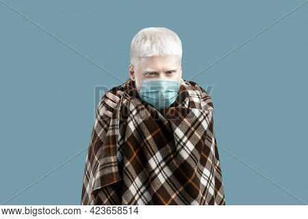 Albino Man With Pale Skin And White Hair Wearing Protective Mask And Wrapped In Blanket, Feeling Unw