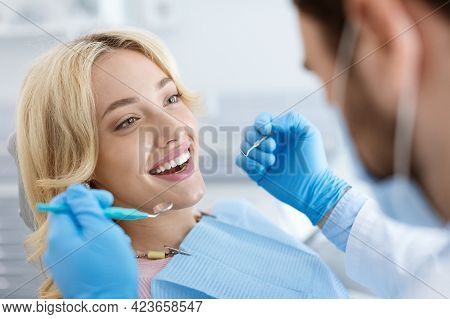 Male Dentist In Face Mask Doing Treatment For Cheerful Lady