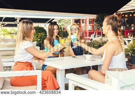Happy Young Girl Friends Toasting Cocktail Drinks At Trendy Pub Restaurant - Lifestyle Concept With