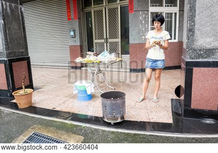 Nantou, Taiwan - August 15th, 2019: woman burning praying cash and put pork, drink and snacks on a table for the
