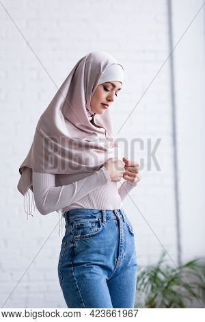 Shy Muslim Woman Touching Hijab While Standing At Home