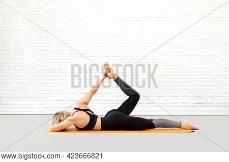 Prep Bow Pose, One Side Extension. Caucasian Attactive Woman In Black Sportswear Lying On The Mat An