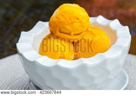 Three Scoops Of Yellow Ice Cream In A White Bowl On Table In Summer Cafe. Mango Flavored Icy Dessert