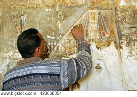 Luxor, Egypt - January 4, 2006: A Restorer Working On A Painted Bas Relief Sculpture In The Ancient