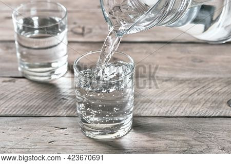 Water Pouring Into Glass. Glass Of Water On Wooden Table, Selective Focus, Close Up. Clear Purified