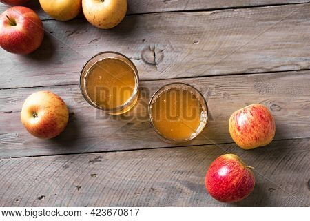 Apple Cider Or Juice Drink And Apples On Wooden Background, Top View, Copy Space. Garden Organic Red