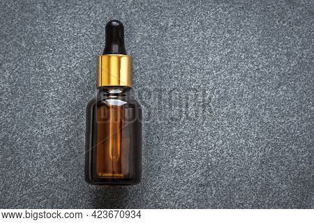 Serum Bottle On Dark Grey Stone Background, Copy Space. Essential Oil, Fluid, Extract Or Skincare Se