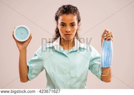 Portrait Of Serious Nurse Who Is Holding Protective Workwear And Clock That Shows Five To Twelve Tim