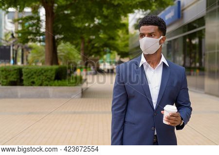 Portrait Of African Businessman Wearing Face Mask Outdoors And Holding Take Away Coffee Cup