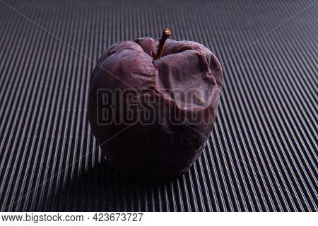 One Dark Rotten Spoiled Apple On Black Background.
