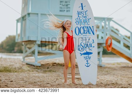 Young Pretty Blond Girl In Red Bikini Posing With Surfboards Against Blue Lifeguard Tower On The San