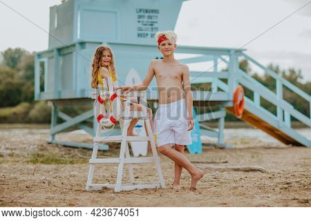 Cute Teen Boy And Young Pretty Girl In Summer Clothes Posing Against Blue Lifeguard Tower On The San