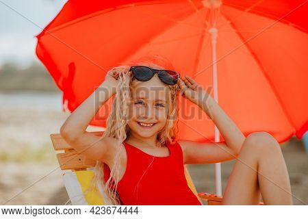 Young Pretty Girl In Summer Bikini Laying On Beach Chair With Red Umbrella And Posing With Sunglasse