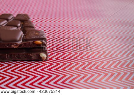 Close-up Cut Chocolate Bar Pieces With Nuts On Red And White Background.