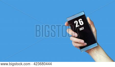 July 26. 26th Day Of The Month, Calendar Date.woman's Hand Holds Mobile Phone With Blank Screen On B