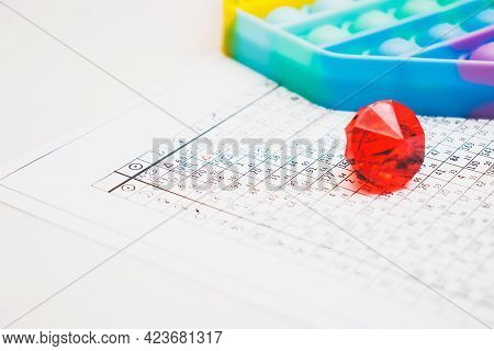 Modern Astrologer's Desktop. Pop It And A Red Glass Pebble On The Table. Astrological Charts And Tab