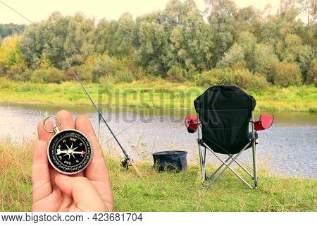Ound Compass In Hand Against Background Of Summer Landscape On River Fishing As Symbol Of Tourism Wi