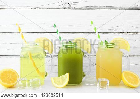 Set Of Summer Iced Green Teas In Mason Jar Glasses With Paper Straws Against A White Wood Background