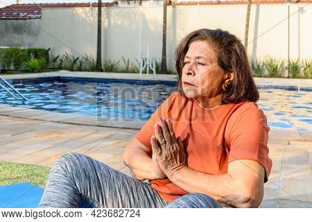 74-year-old Elderly Woman Practicing Yoga With Her Eyes Closed At The Edge Of The Pool.