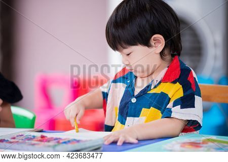 Adorable Asian Boy Is Painting Chalk Color With His Right Hand. Children Paint Art At Home. Cute Bab