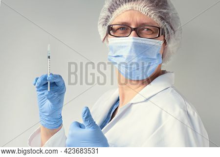 Coronavirus Vaccine Ok. Medic In Face Mask, Glasses And Disposable Hat, Blue Nitril Gloves And Prote